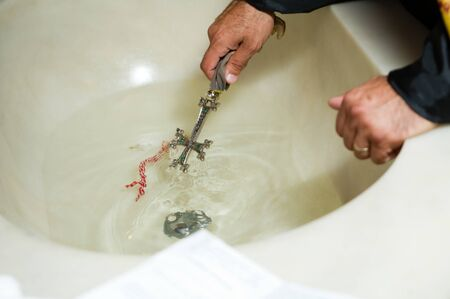 priest dips a large cross in a sink with water during the rite. close up Фото со стока