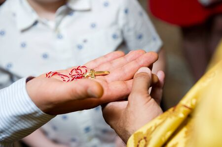 a golden cross on a red and white thread lies on the hand held by the priest. Close-up