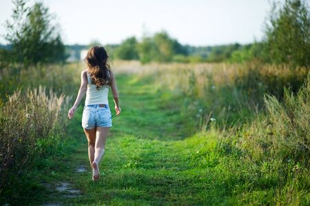 girl in denim shorts with her hair running away barefoot along a country road. copy space 免版税图像