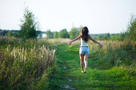 girl in denim shorts with her hair running away barefoot along a country road. copy space Stockfoto