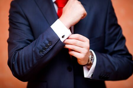 the groom defiantly straightens the cufflink on the shirt, the sleeve of which peeps from under the jacket, close-up