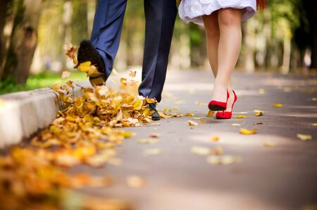 the couple walks through the park in the autumn and throws their fallen leaves into the air with their feet. Kicking the leaves. Close-up, no faces Stok Fotoğraf