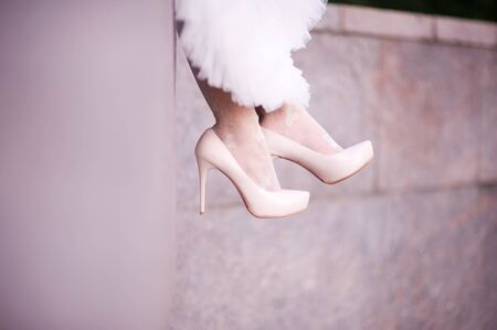 close-up of the bride s legs in shoes, which sits on the parapet, legs hanging down. Copy space Archivio Fotografico - 129688672