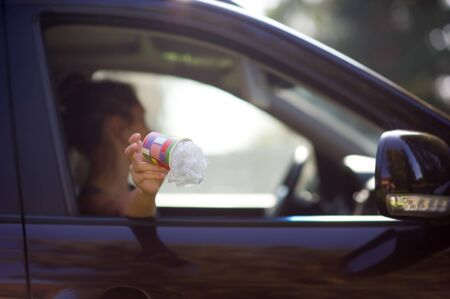 A young woman throws waste from the car - a coffee cup and a bag. Environmental pollution, selective focus, backlight. Copy space