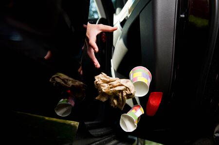 a female hand throws a handful of garbage accumulated in the car at the open door of the car - coffee glasses, bags, crumpled paper. Flying objects are slightly blurred to enhance the effect of movement. Close up
