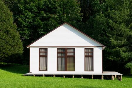 small white house with curtained windows stands on a small slope, front view. close up