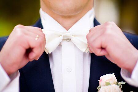 Nahaufnahme eines Bräutigams, der eine Fliege am Hals ausrichtet. kein Gesicht