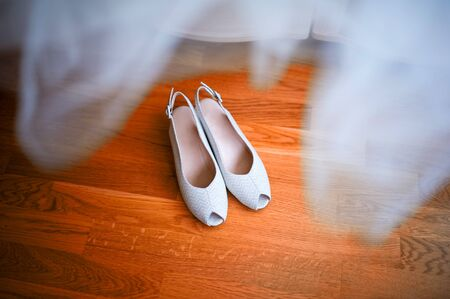 shoes of the bride stand on a wooden floor, top view. Bridesmaid dress hanging over the shoes
