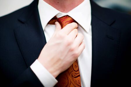 close-up of a man in a jacket and shirt straightens his tie Imagens