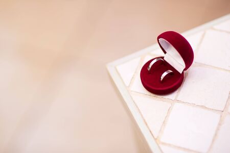 red box with wedding rings on the edge of a table copy space Imagens