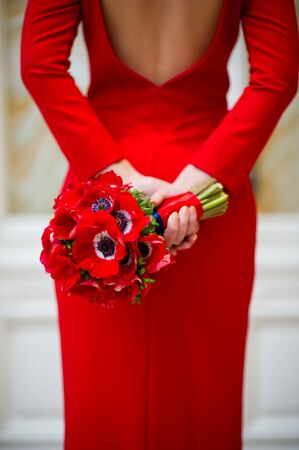 girl in a red dress holds a red bouquet bouquet behind. Vertical frame