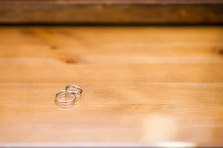 two wedding rings lie on a polished wooden surface. copy space