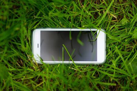 A white mobile phone with a dark screen lies in the green grass with the screen up. Smartphone in the meadow. close up