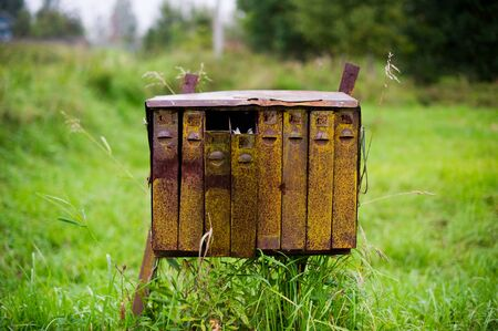 Closeup of old rusty mailboxes in a village. Two of them are open