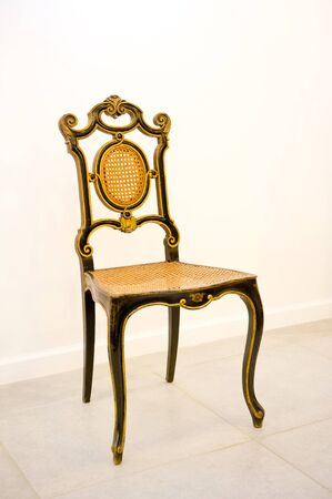 an antique chair in black and gold stands against the wall. Vertical photography
