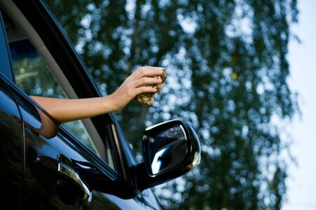 A young woman is about to throw a crumpled piece of paper or packaging from a sandwich into an open car window. View from below, on the background of blurry trees and sky. Copy space