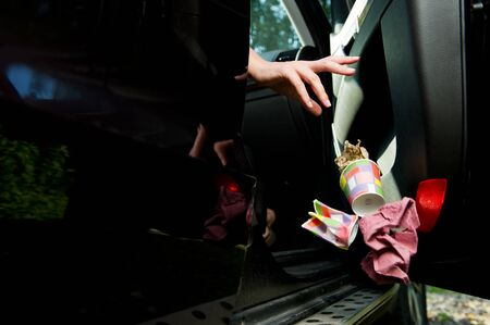 a female hand throws a handful of garbage accumulated in the car at the open door of the car - coffee glasses, bags, crumpled paper. Flying objects are slightly blurred to enhance the effect of movement. Close up Imagens