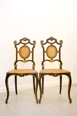 two antique chairs in black and golden color stand against the wall. Vertical photography