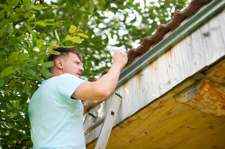 master at work. the homeowner concentrates on the roof of his house to measure the gutter Imagens
