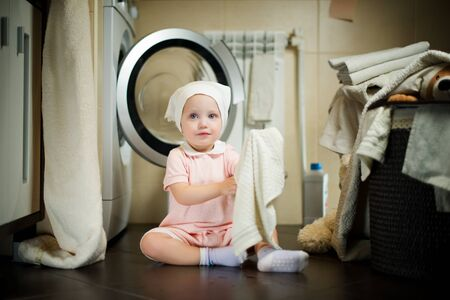baby girl sitting on the floor near the washing machine in the bathroom with a towel in her hand Imagens