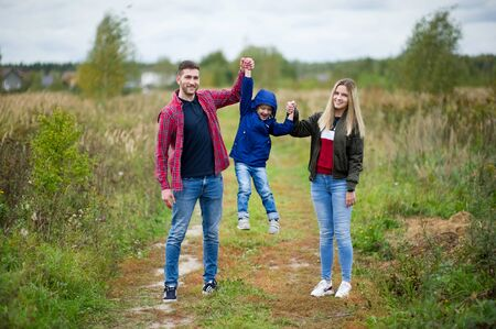 Young parents with their son play on a country road, raising his hands in the air
