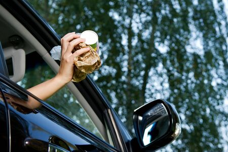 The girl is going to throw a handful of garbage accumulated in the car into the open window of the car - coffee glasses, bags, crumpled paper. Bottom view, against the background of blurry trees and sky, summer day