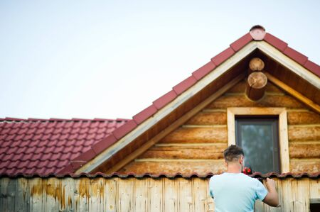 a man in a white T-shirt sets elements on the roof of a wooden house