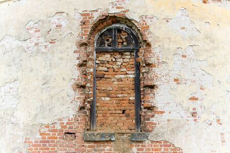 bricked window of an old abandoned church and a wall with crumbling plaster