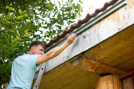 Man at work. the man is concentrated, he puts the markup to install the gutter on a wooden house