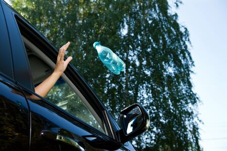 A girl throws an empty plastic bottle into the open window of a car. A flying object is slightly blurred. Bottom view, against the background of blurry trees and sky, summer day
