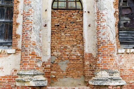 wall of an abandoned building, the entrance to which is bricked up, and the windows are boarded up