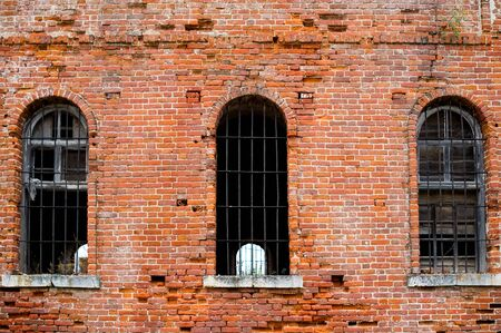 brick wall of an old abandoned prison with bars on the windows