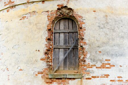 window of an old abandoned church boarded up with wooden boards and a wall with crumbling plaster