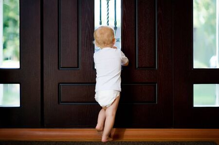 the child is waiting near the front door to be picked up and looks out the window into the street. Back view