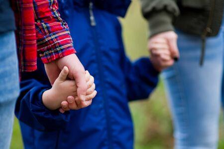Parents hold their hands. Close-up, without faces. Focus on the hands