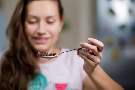 Young woman holds in the air a spoon with chocolate flakes and milk, about to eat them. front view