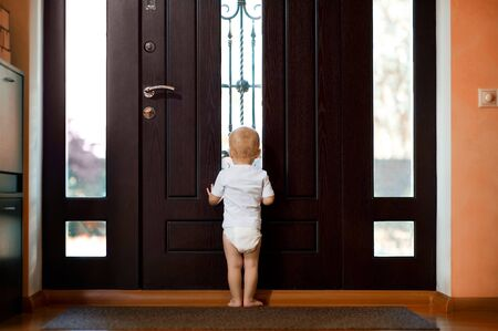 little girl waiting near the front door of mom and dad. Back view