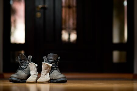 Adult and children's leather winter shoes standing in a dark corridor. Copy space