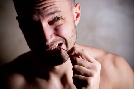 stern man cleans the space between the teeth with a toothpick, side lighting, contrast light