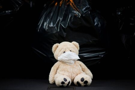A teddy bear in a gauze medical bandage sits on the background of large garbage bags in the trunk of a car