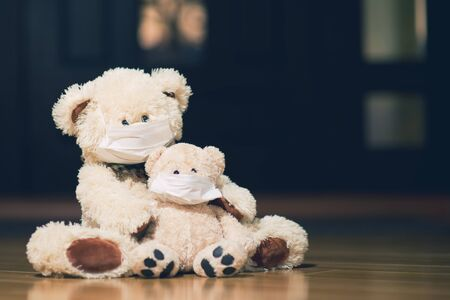 Teddy bears in medical masks are sitting near the front door in the hallway of the house. Toned