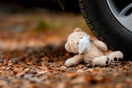 close-up of a teddy bear in a medical mask crushed by a car