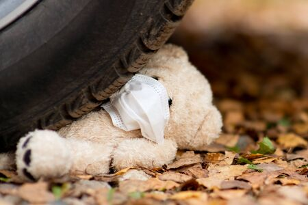 a teddy bear with a medical bandage on his face is crushed by a car wheel, close up Reklamní fotografie