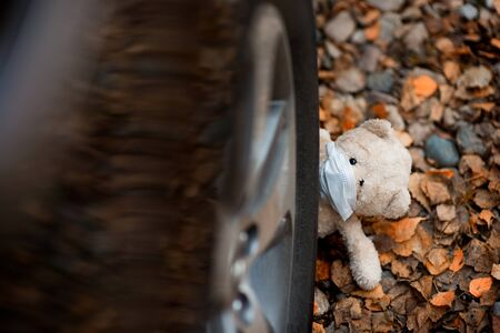 a teddy bear in a medical mask sadly looks out from under the wheel of the car that crushed him Reklamní fotografie