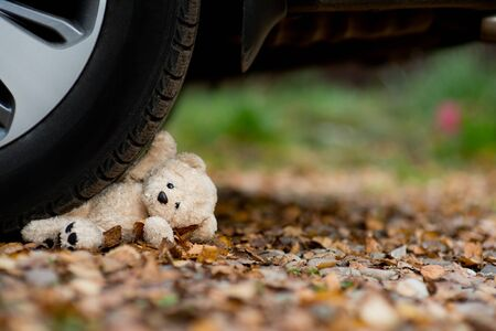 little teddy bear under the car wheel