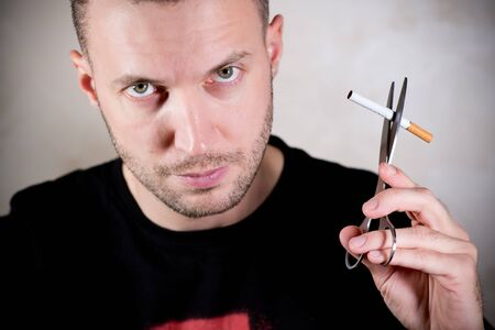 young unshaved man holding a cigarette next to himself with scissors, about to cut a cigarette