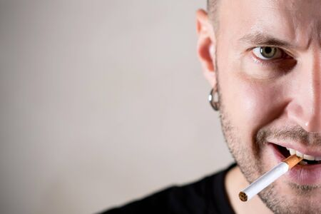 brutal green-eyed man with a piercing with a three-day stubble is about to light a cigarette, holding a lit lighter in front of him