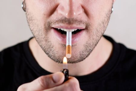 an unshaven handsome man is about to light a cigarette with a lighter, taking it in his mouth with the wrong side. Without eyes, lower half of the face