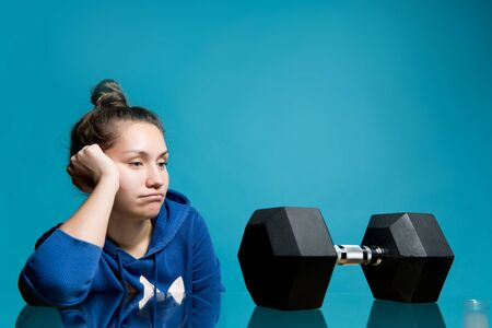 the girl looks in frustration and longing at the big dumbbell lying in front of her, close up