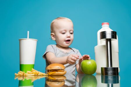 a little girl chose healthy food instead of harmful and grabs an apple. On the opposite side is a soda, burger and french fries